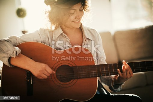 istock Young guitarist practising at home 936738912