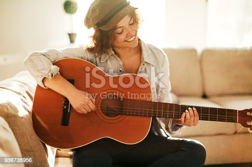 istock Young guitarist practising at home 936738956