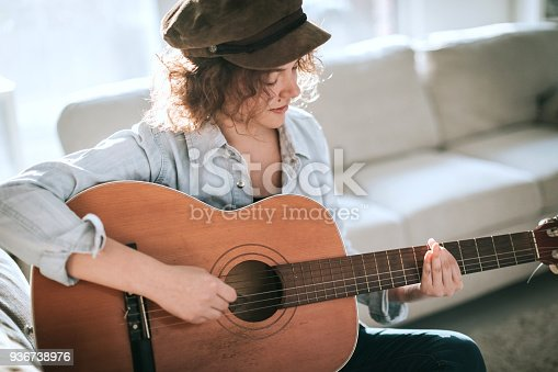 istock Young guitarist practising at home 936738976