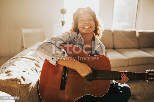 istock Young guitarist practising at home 936738984