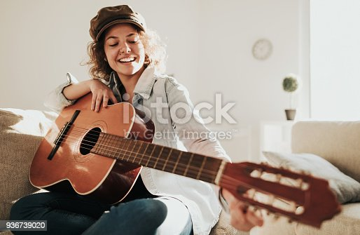 istock Young guitarist practising at home 936739020