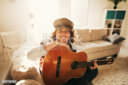 istock Young guitarist practising at home 936739060
