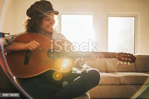 istock Young guitarist practising at home 936739082