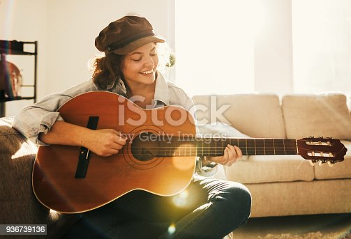 istock Young guitarist practising at home 936739136