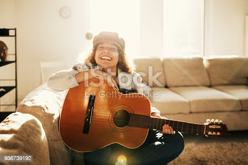 istock Young guitarist practising at home 936739192