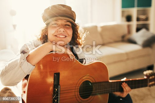 istock Young guitarist practising at home 936739220