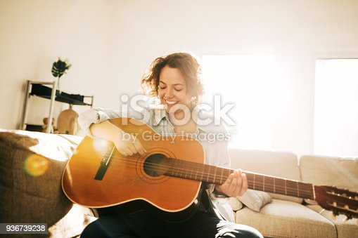 istock Young guitarist practising at home 936739238