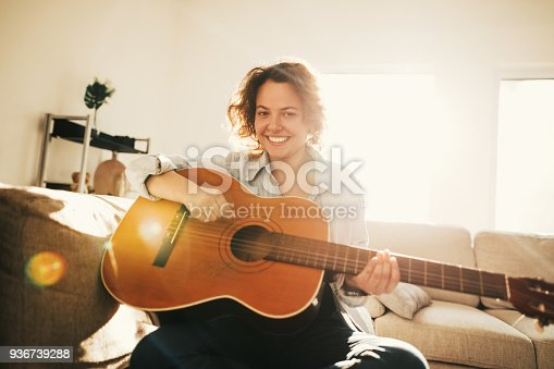 istock Young guitarist practising at home 936739288