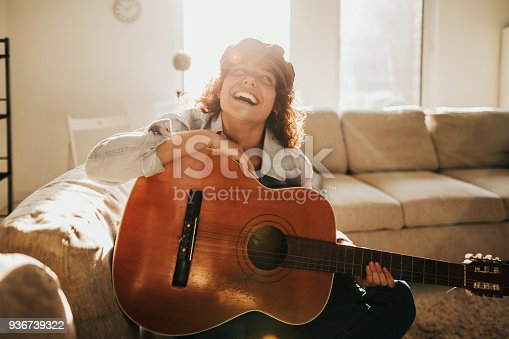 istock Young guitarist practising at home 936739322