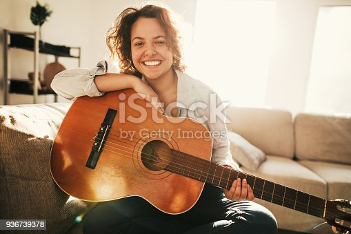 istock Young guitarist practising at home 936739378