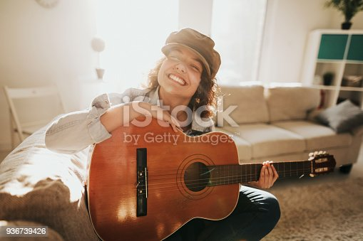 istock Young guitarist practising at home 936739426