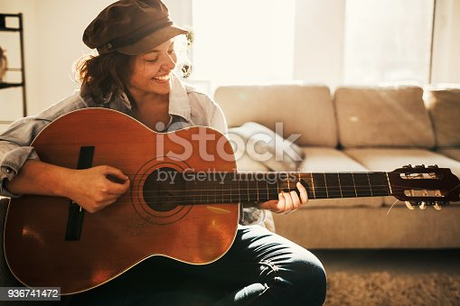 istock Young guitarist practising at home 936741472