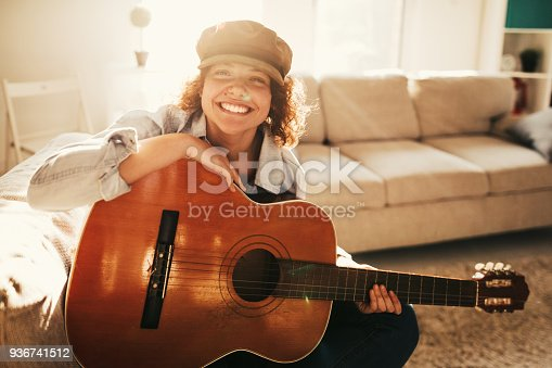 istock Young guitarist practising at home 936741512