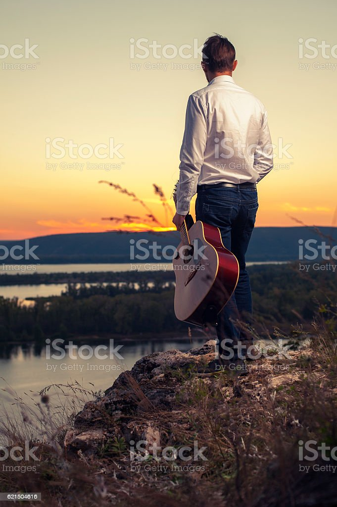 Young guitarist standing on the river bank Lizenzfreies stock-foto