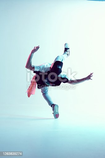 Young guy breakdancer performs trick in jump dancing in studio in neon light. Break dance lessons. Dance school poster. High quality photo