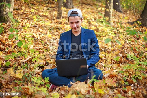 944992706 istock photo Young guy businessman in classic blue jacket with laptop sitting in forest park in autumn 1184010842