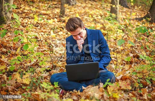 944992706 istock photo Young guy businessman in classic blue jacket with laptop sitting in forest park in autumn 1184010848