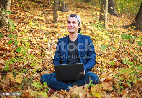 944992706 istock photo Young guy businessman in classic blue jacket with laptop sitting in forest park in autumn 1184010850