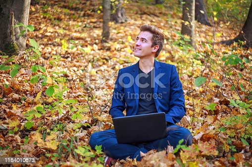 944992706 istock photo Young guy businessman in classic blue jacket with laptop sitting in forest park in autumn 1184010873