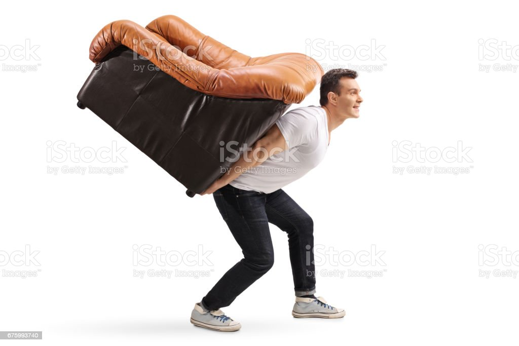 Young guy carrying an armchair on his back stock photo