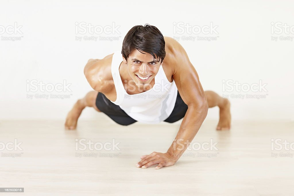 Young guy doing single hand push ups at a gym royalty-free stock photo