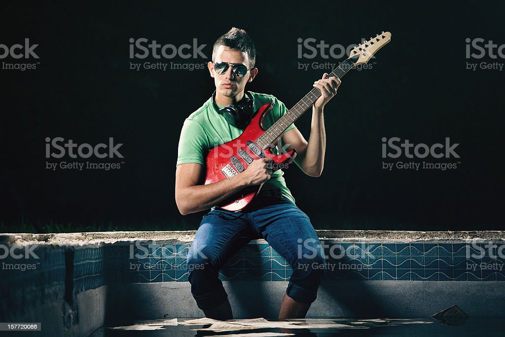 rock \'n\' pool - young man plays an electric guitar sitting by a...