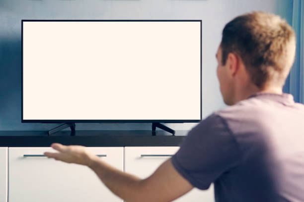young guy emotionally watching TV and waving his hands in discontent. Blank white screen for design. stock photo