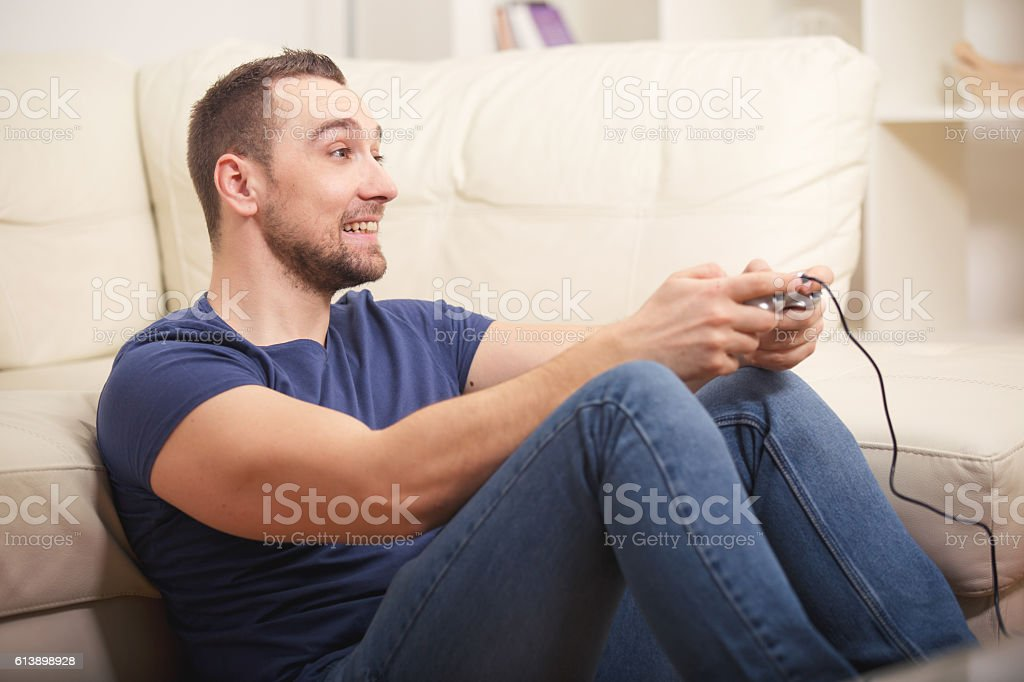 Young guy enjoying computer game, playing with joystick stock photo
