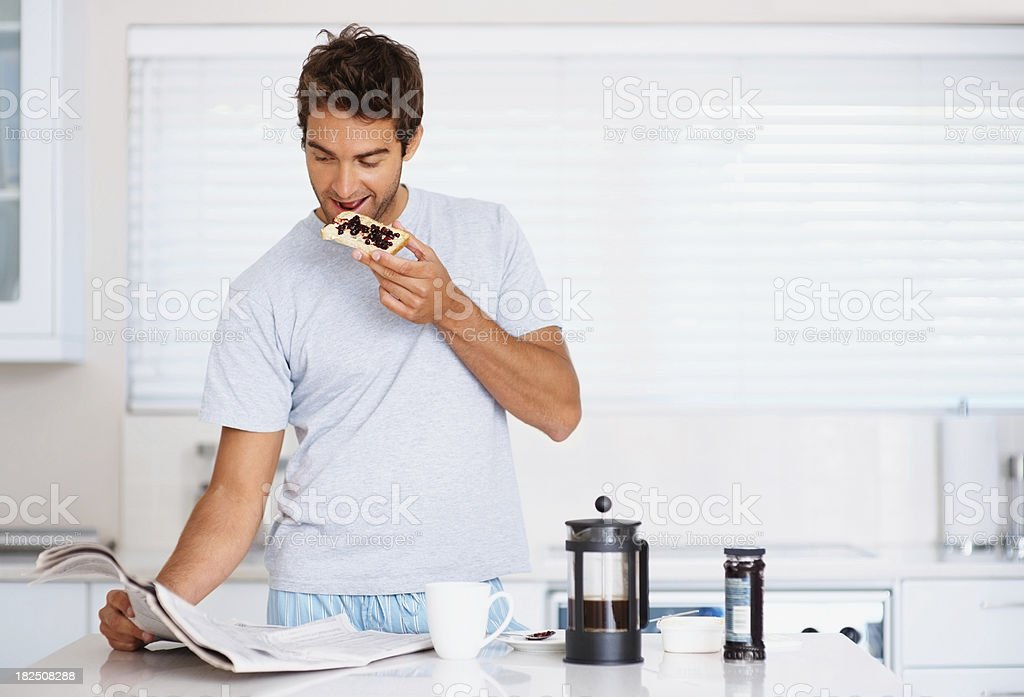 Young guy having a breakfast white reading newspaper stock photo