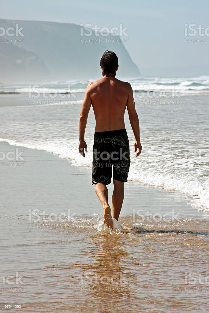 Young guy having a walk at the beach royalty-free stock photo