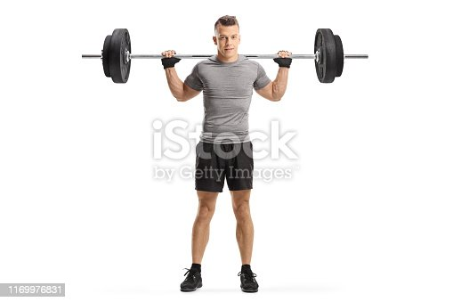 Full length portrait of a young guy holding weights on shoulders isolated on white background