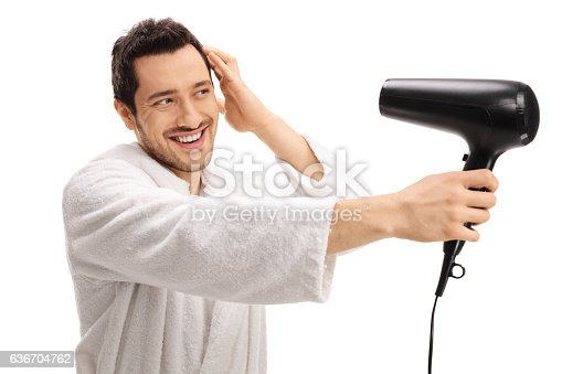 639833996istockphoto Young guy in a bathrobe drying his hair with hairdryer 636704762
