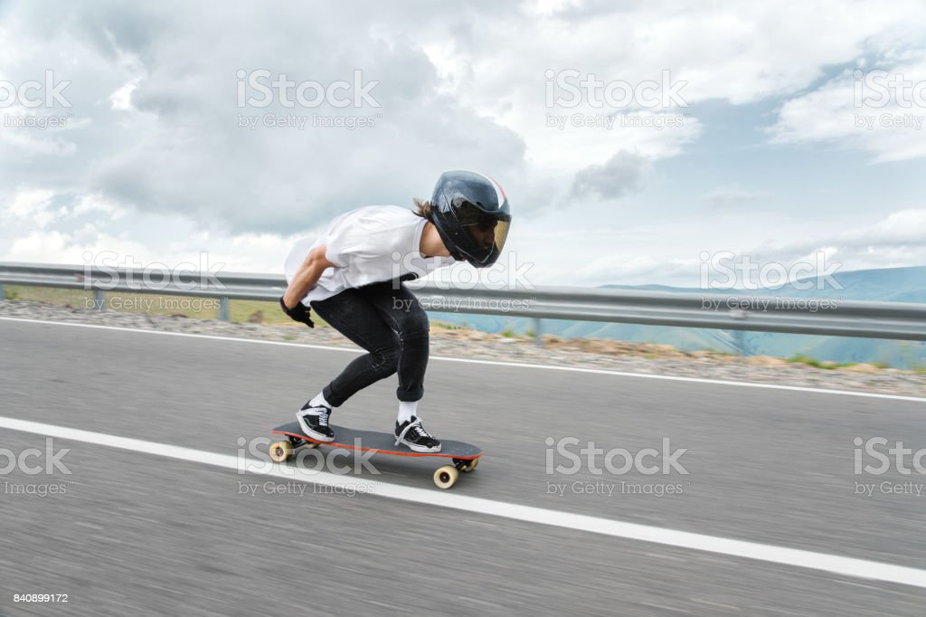A young guy in a full-face helmet is riding on a country road at high speed in the rain stock photo
