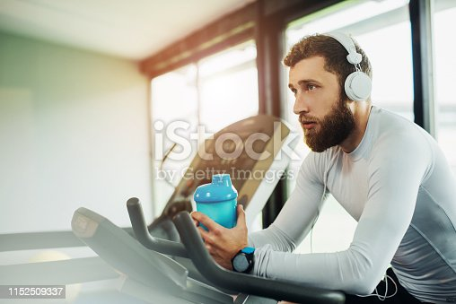 istock Young guy in a gym exercise 1152509337