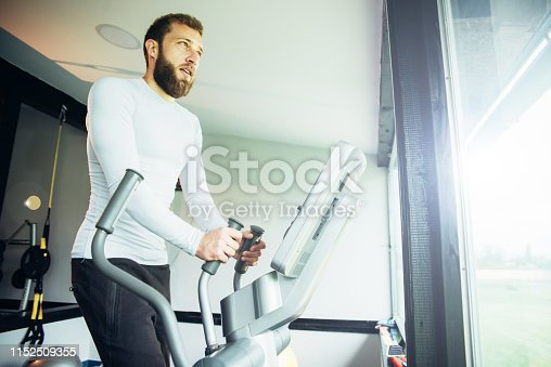 istock Young guy in a gym exercise 1152509355