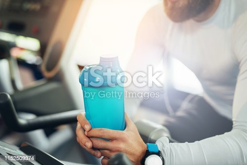 istock Young guy in a gym exercise 1152509374