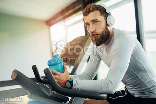 istock Young guy in a gym exercise 1152509388