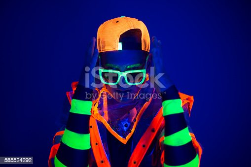 istock Young guy in creative costume with neon glow. 585524292