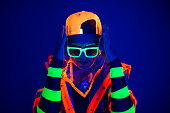 A young guy in a creative costume with neon glow on a blue background.