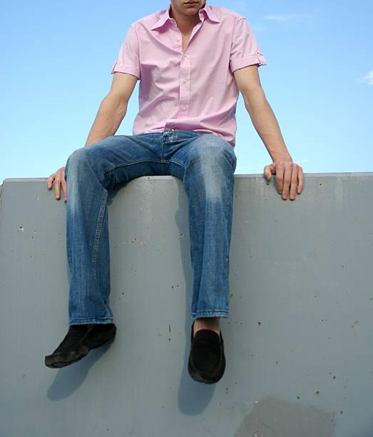 Cara jovem na Camisa cor-de-rosa Preppie fica na parede - foto de acervo