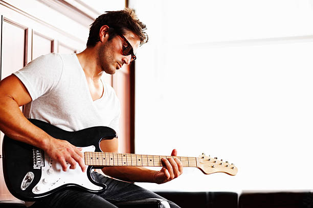 Young guy in sunglasses playing guitar stock photo
