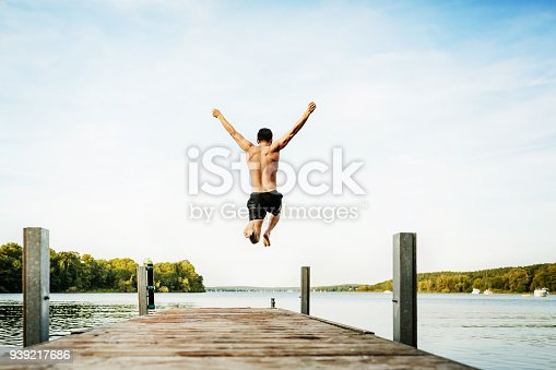Young man jumping with his arms in the air off the end of a jetty at a lake