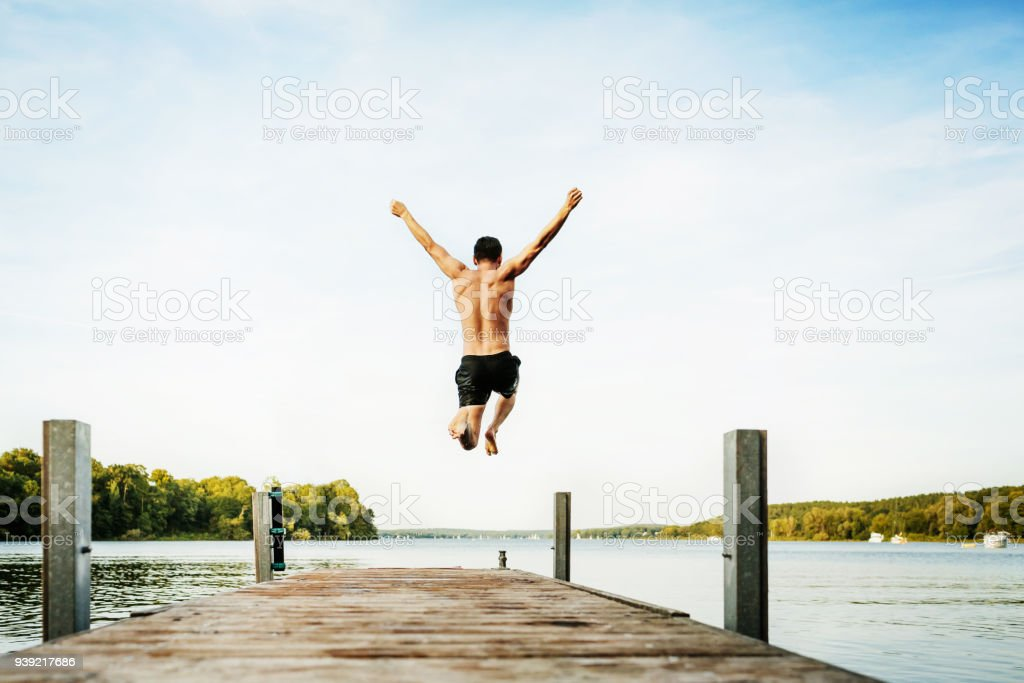 Young guy Jumping Off Jetty At Lake stock photo