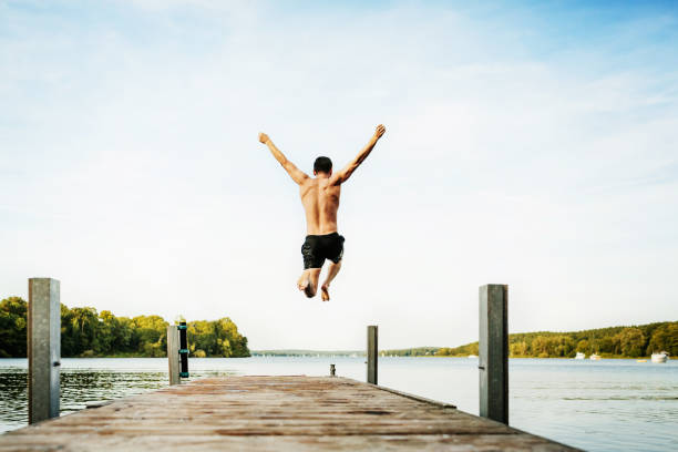 young guy jumping off jetty at lake - jumping into water stock pictures, royalty-free photos & images
