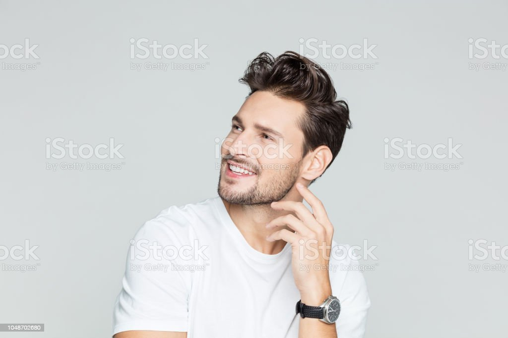 Young guy looking away and smiling Portrait of young caucasian man with beard looking away and  smiling on grey background 25-29 Years Stock Photo