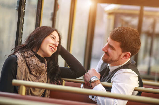 Young guy meets and talks to girl in tram public transport cabin Young guy meets and talks to a girl in the tram public transport cabin stranger stock pictures, royalty-free photos & images