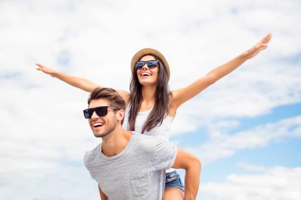 junger kerl huckepack fröhlich freundin wie flugzeug auf dem hintergrund des himmels - mädchen wochenende stock-fotos und bilder