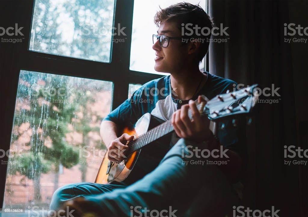 Junge Kerl Plaing an der Gitarre und sitzt am Fenster – Foto