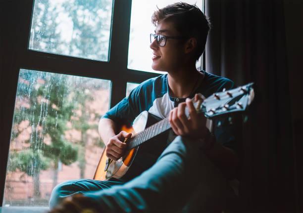junge kerl plaing an der gitarre und sitzt am fenster - one song training stock-fotos und bilder