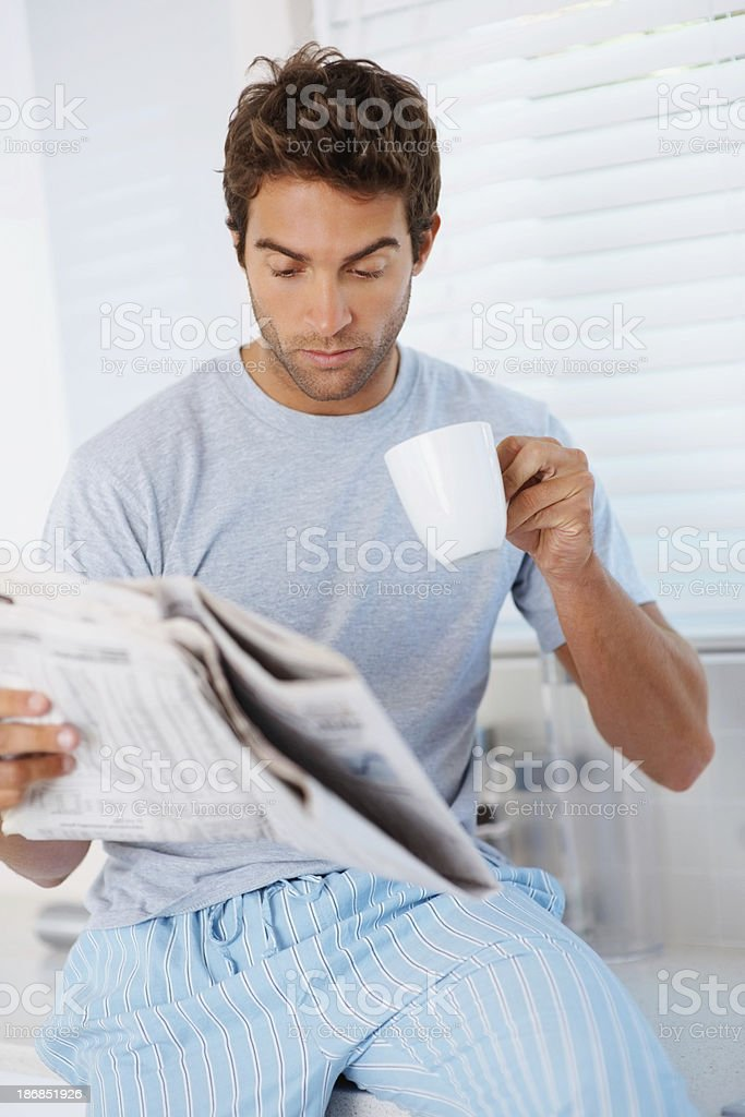 Young guy reading the newspaper and drinking coffee royalty-free stock photo
